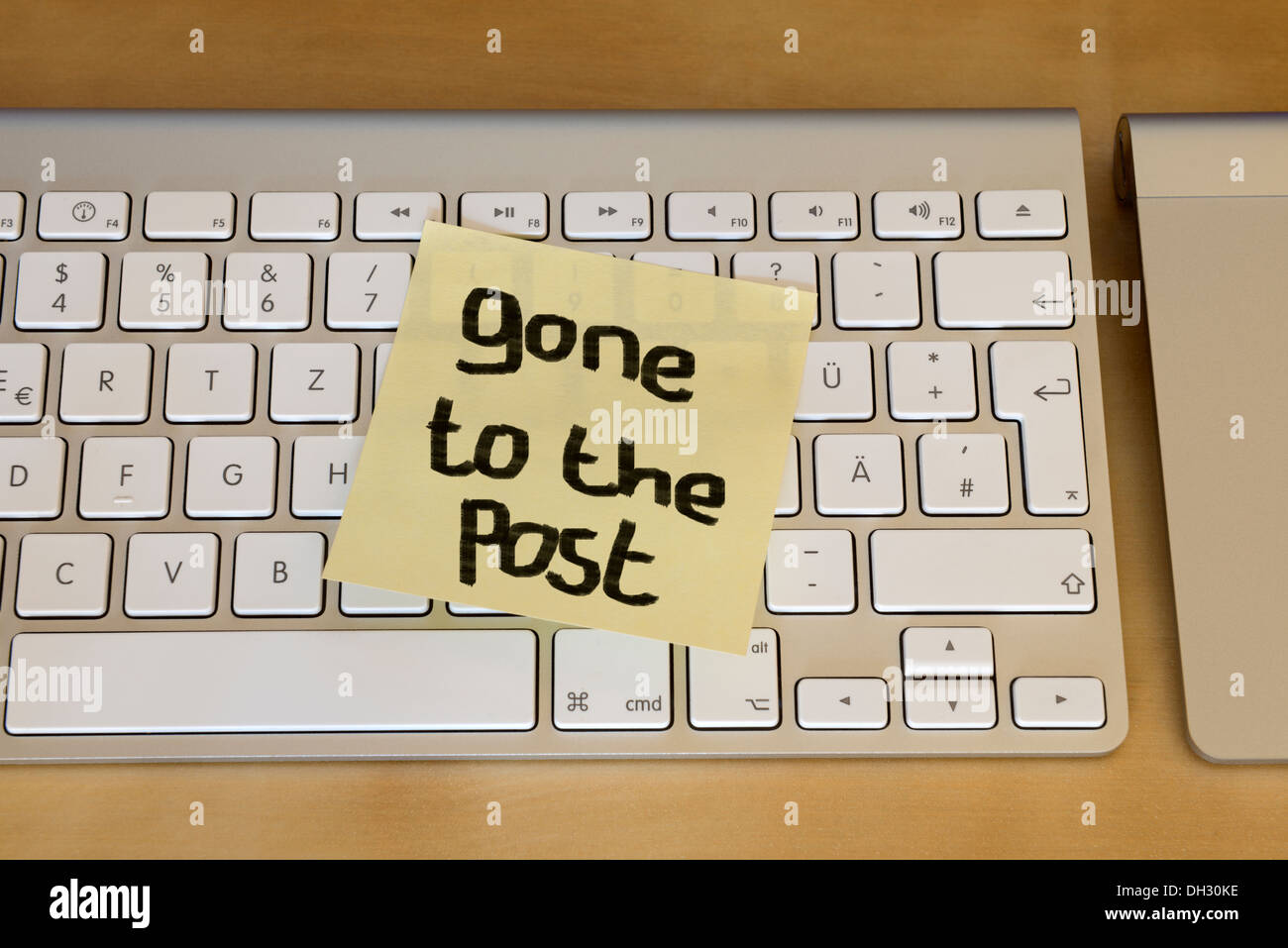 'Gone to the post' post-it note stuck on computer keyboard - Stock Image