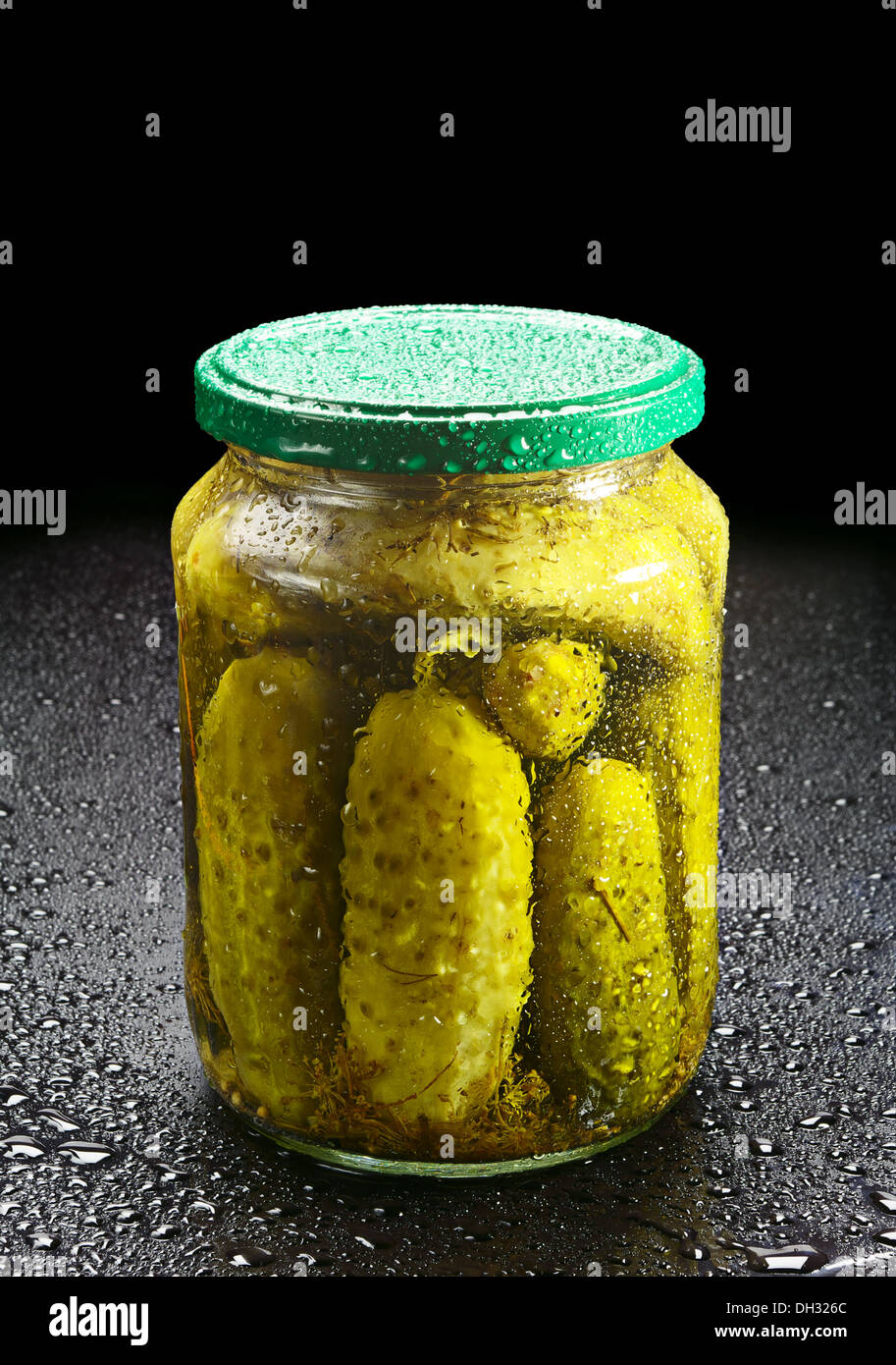Pickled cucumber in glass jar with water drops on black - Stock Image