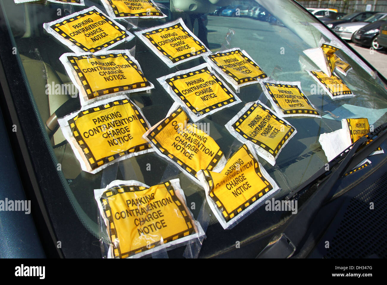 An illegally parked car with multiple parking tickets - Stock Image