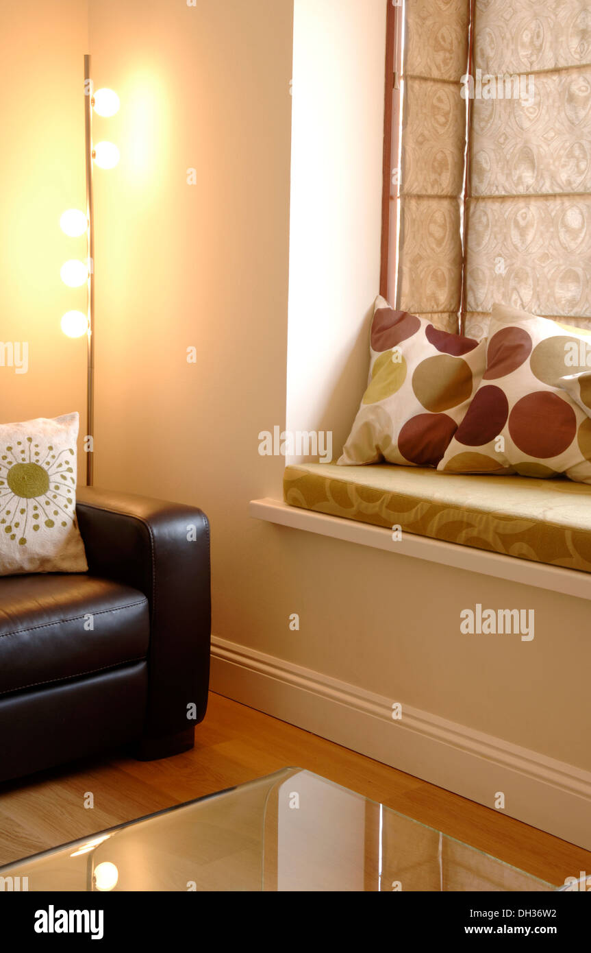 Living room with leather sofa, glass coffee table, polka dot cushions, interesting lamp, wooden floors and a window seat. - Stock Image