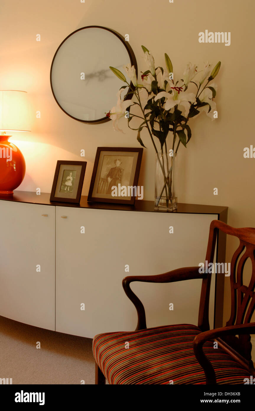 Detail of a living room with designer sideboard or cabinet family photographs a large wall clock, vase of flowers carver chair - Stock Image