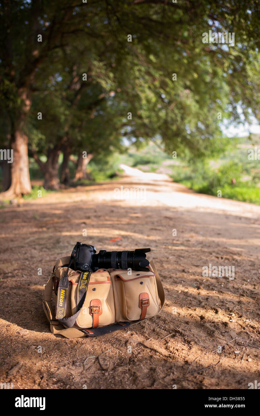 Nikon Camera equipment and bag on a dirt track in the Indian countryside. Andhra Pradesh, India - Stock Image