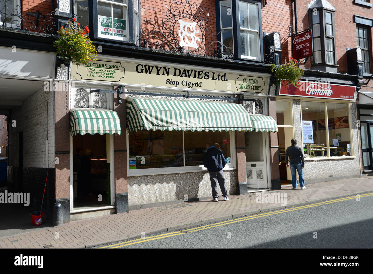 Traditional butcher and baker in the main street of Llangollen with signs in Welsh - Stock Image