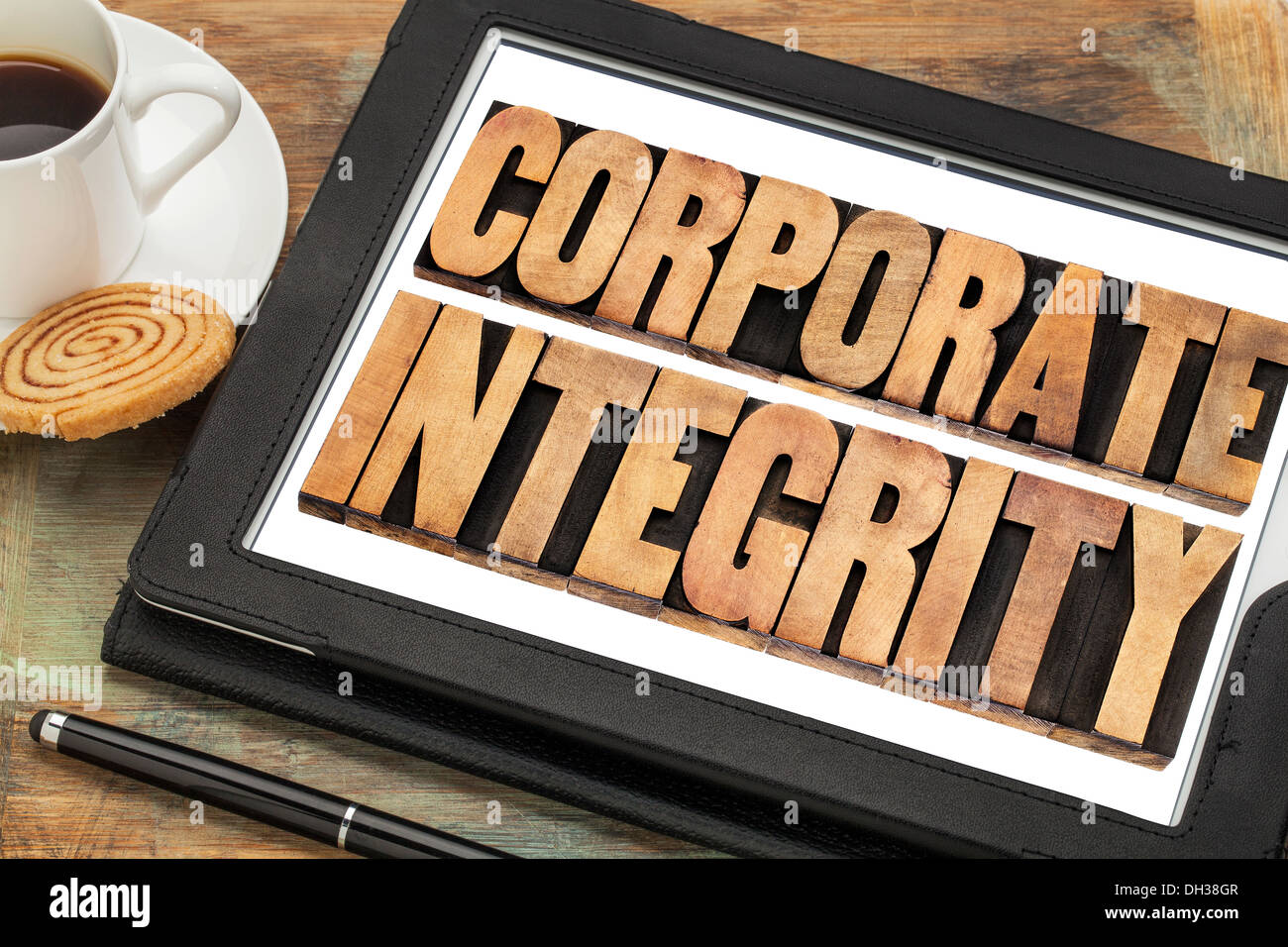 corporate integrity - business ethics concept - text in letterpress wood type on digital tablet computer - Stock Image