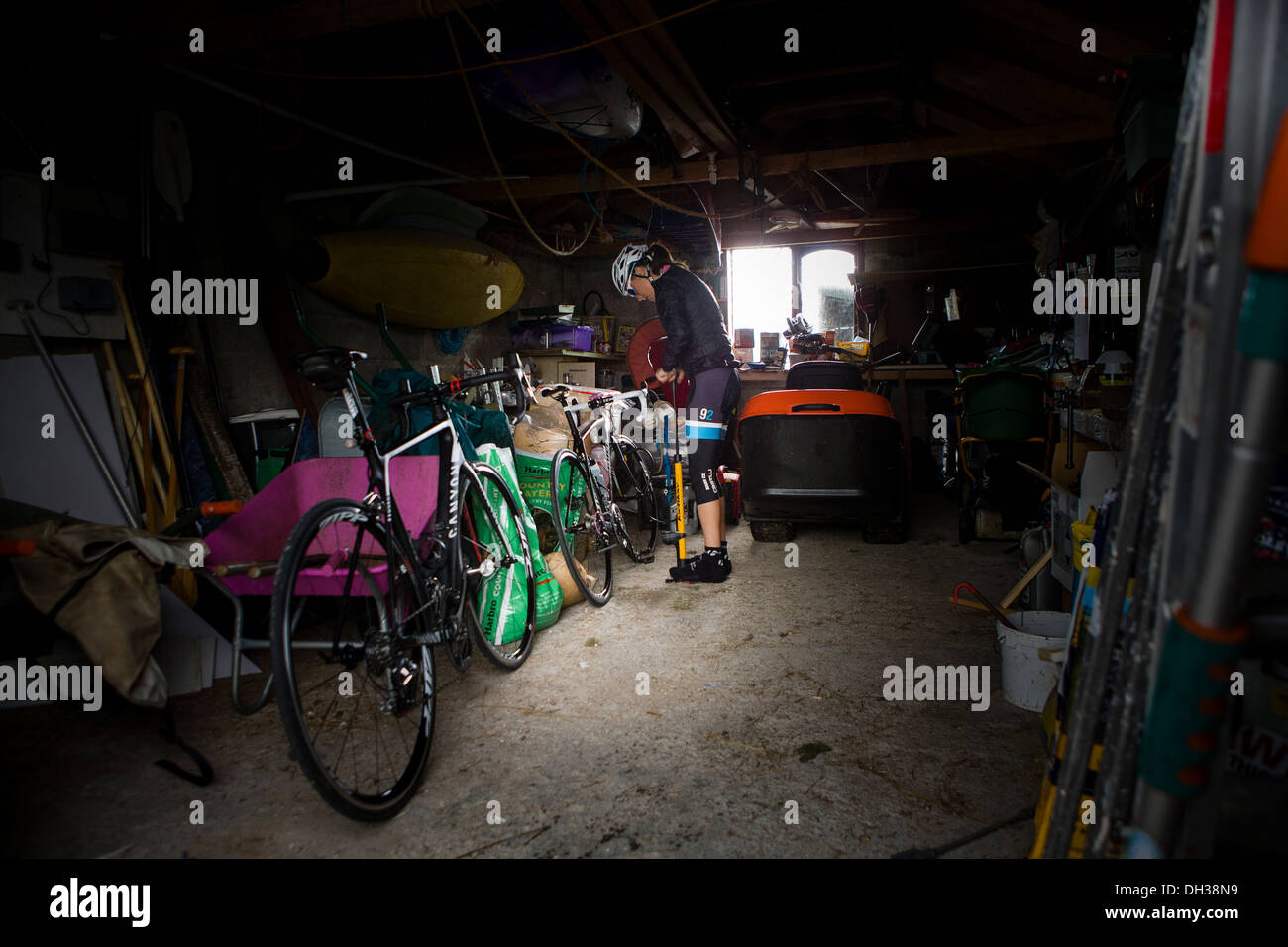 A cyclist stands next to her bicycle in a garage, Scottish Highlands, Scotland, United Kingdom - Stock Image