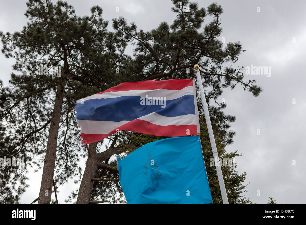 The Thai flag flutters on a flagpole at a UK Thai temple. - Stock Image