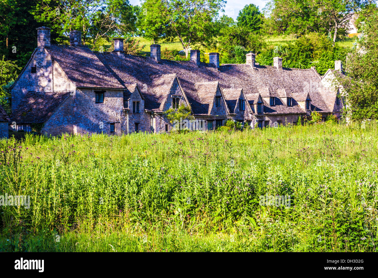 The famous weavers' cottages, Arlington Row, viewed across the Rack Isle, an ancient water meadow, in Bibury, Cotswolds - Stock Image