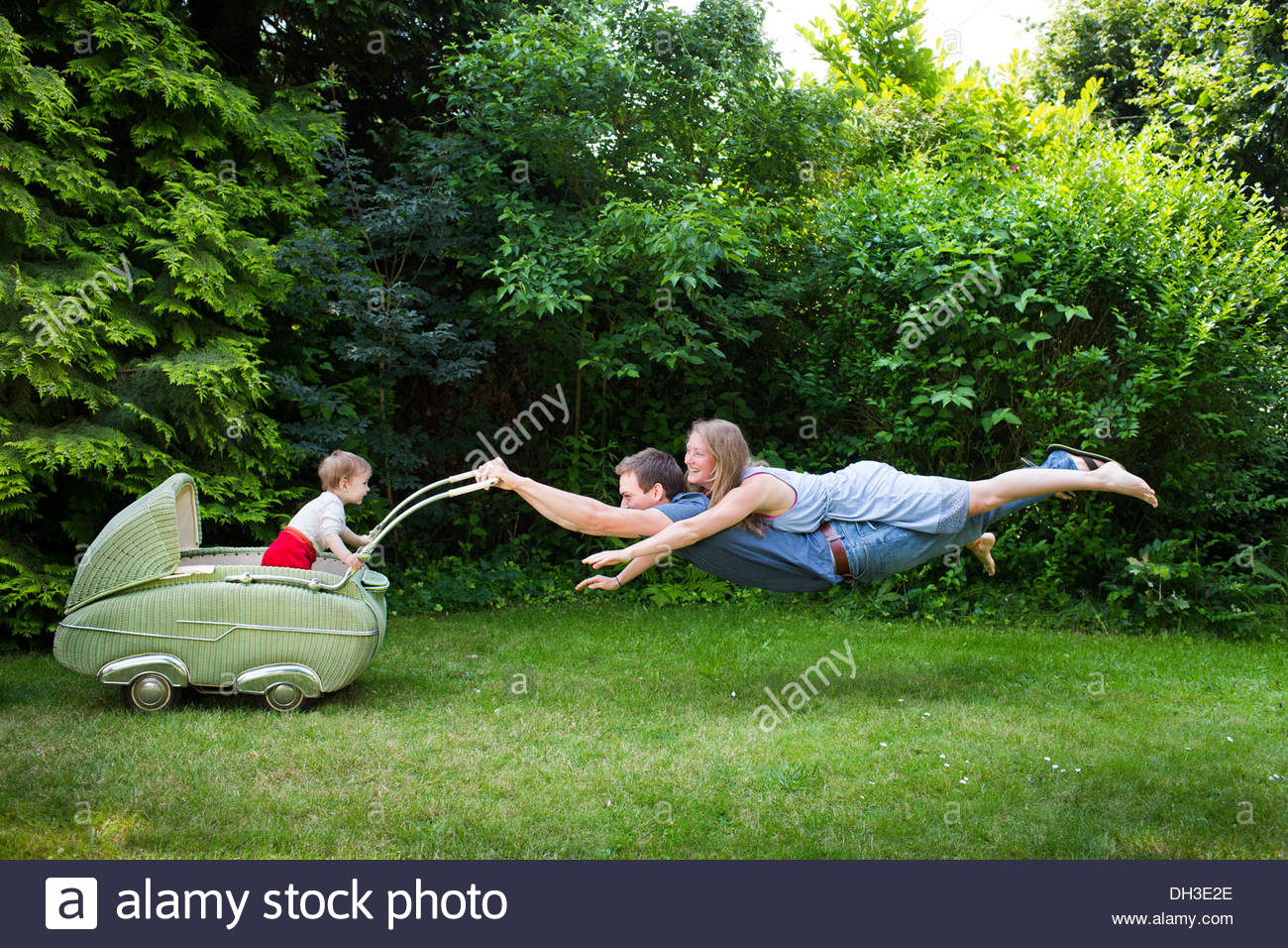 Couple is flying behind a stroller from the 50 s with a one year old child inside - Stock Image