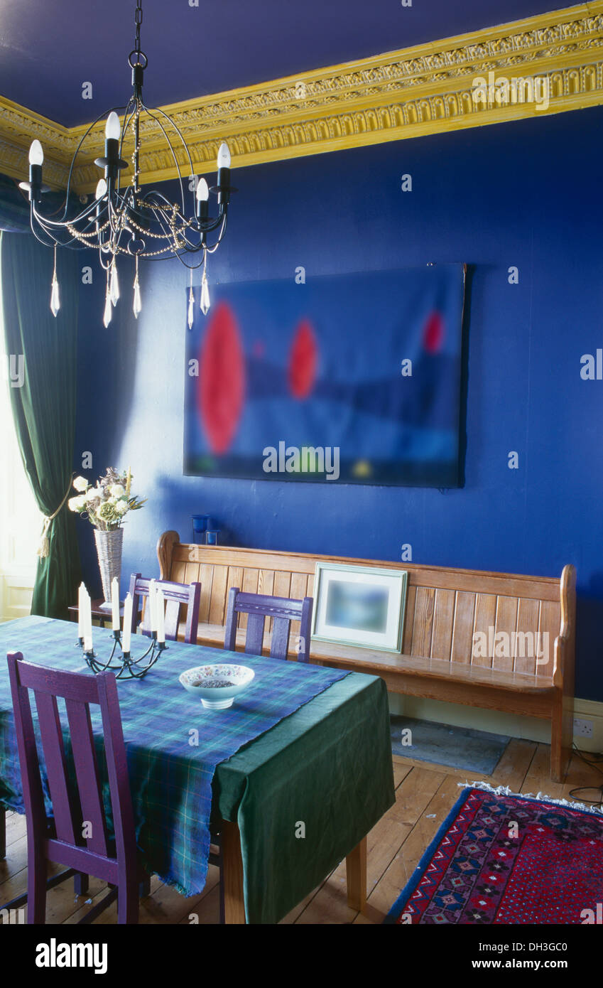 Table With Blue Cloth And Painted Purple Chairs In Bright Blue Dining Room  With Up Cycled Church Pew And Yellow Cornice