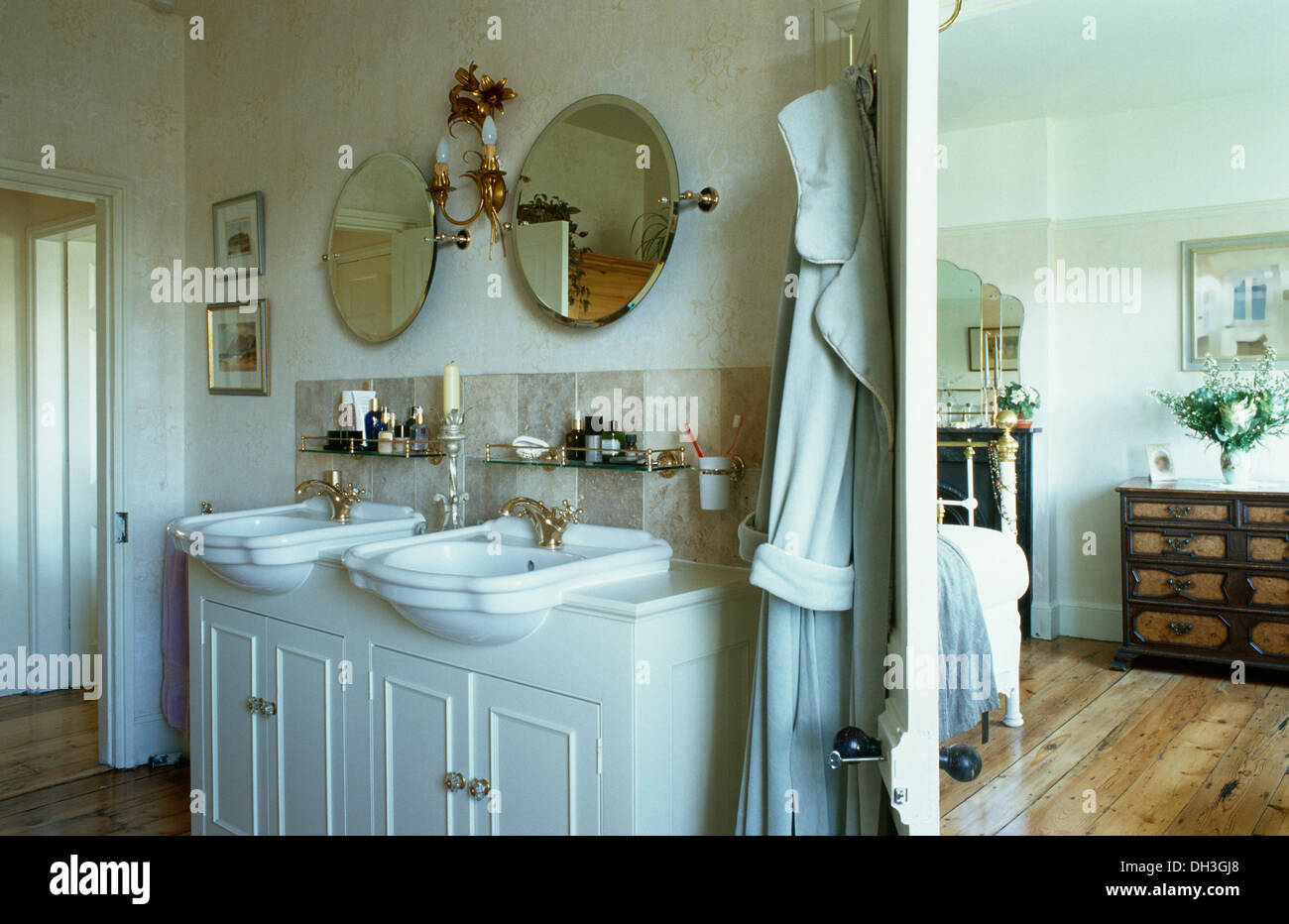 Circular mirrors above vanity unit with double basins beside open ...