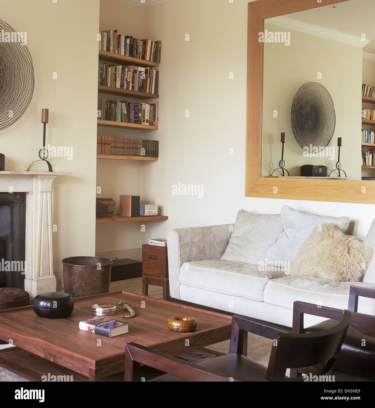 Large plain wood mirror above pale gray sofa in townhouse living ...