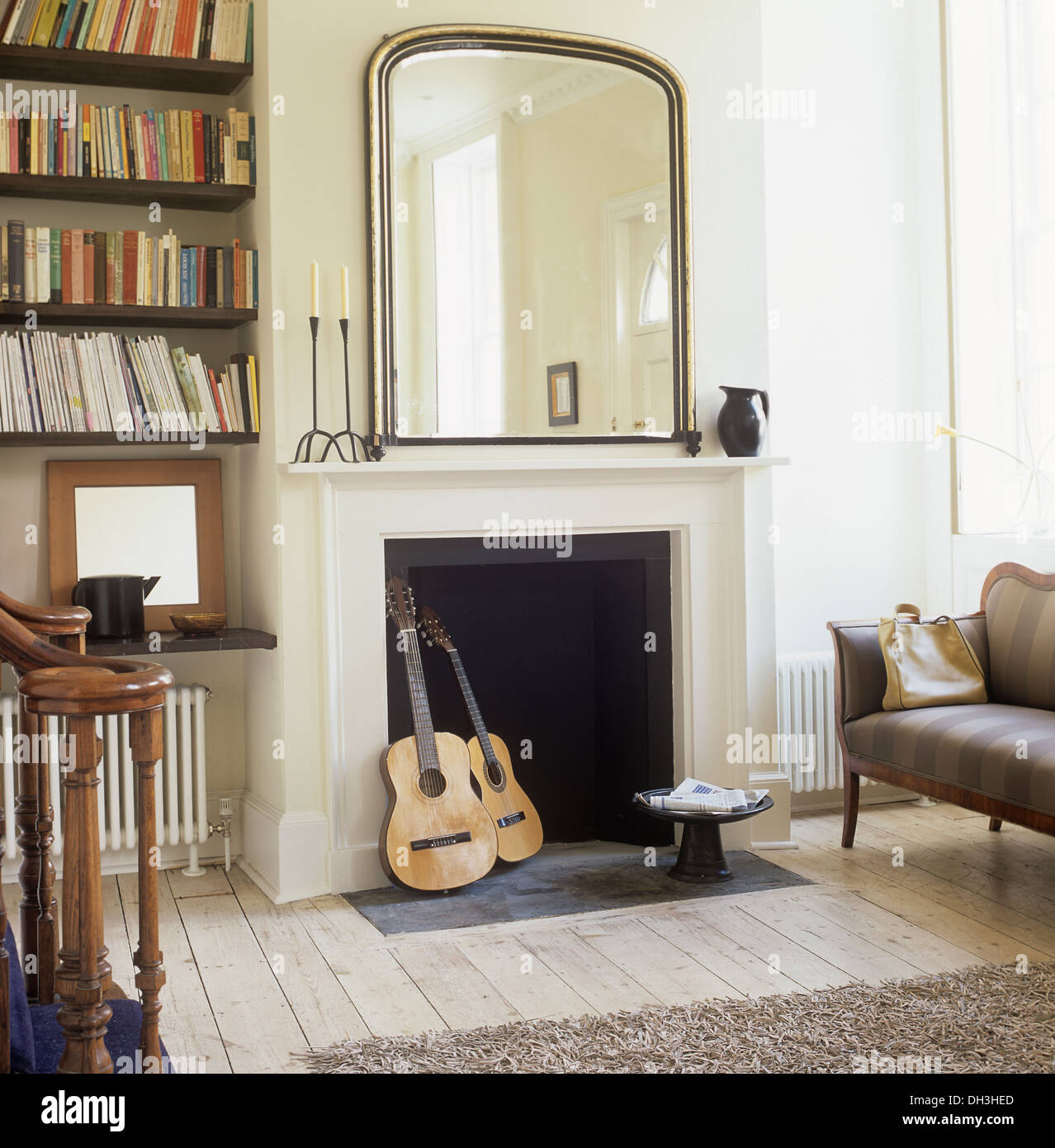 Guitars in a fireplace below large wall mirror in hall living room ...