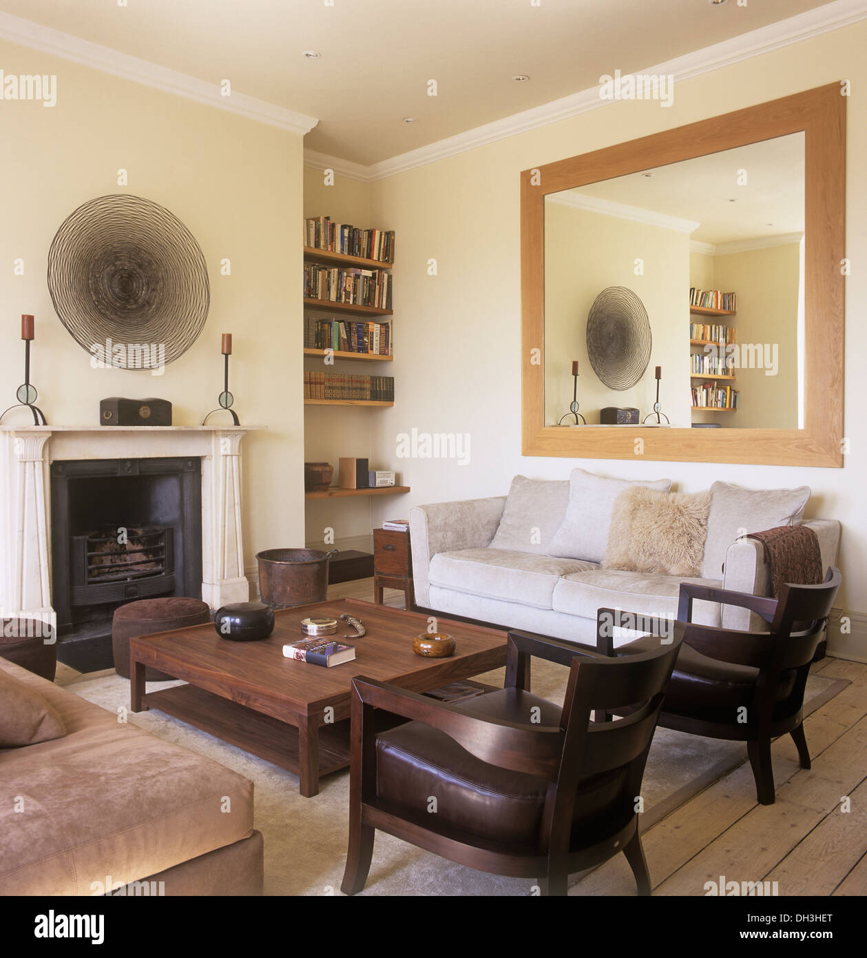 Large Mirror Above Sofa In Townhouse Living Room With Wooden Coffee Table  And Wood+leather Chairs In Front Of Fireplace