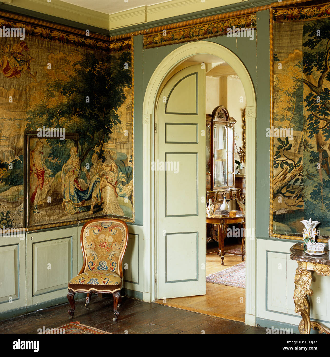 Victorian chair beside arched double doors in country hall with large landscape tapestries covering the walls above dado height & Victorian chair beside arched double doors in country hall with ...