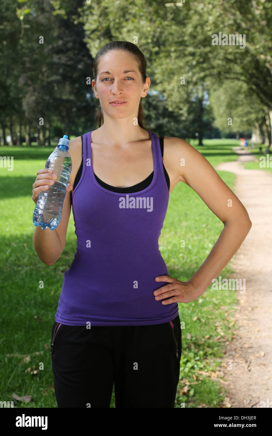 Sporty young woman with water bottle after jogging or running - Stock Image