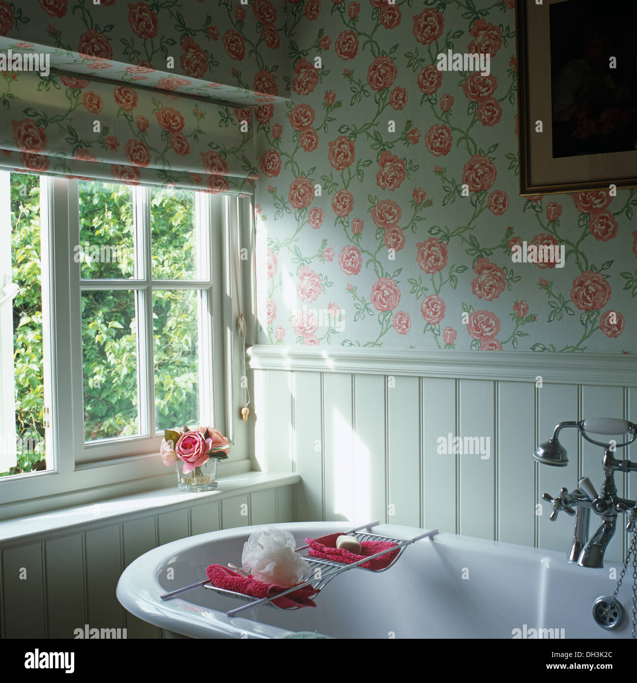. Rose patterned Roman blind and wallpaper in cottage bathroom with
