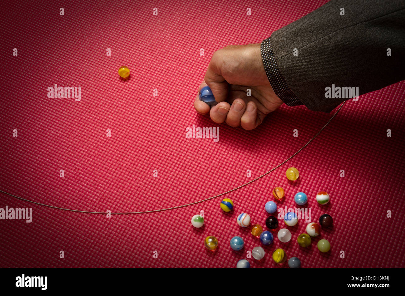 businessman playing marbles - Stock Image