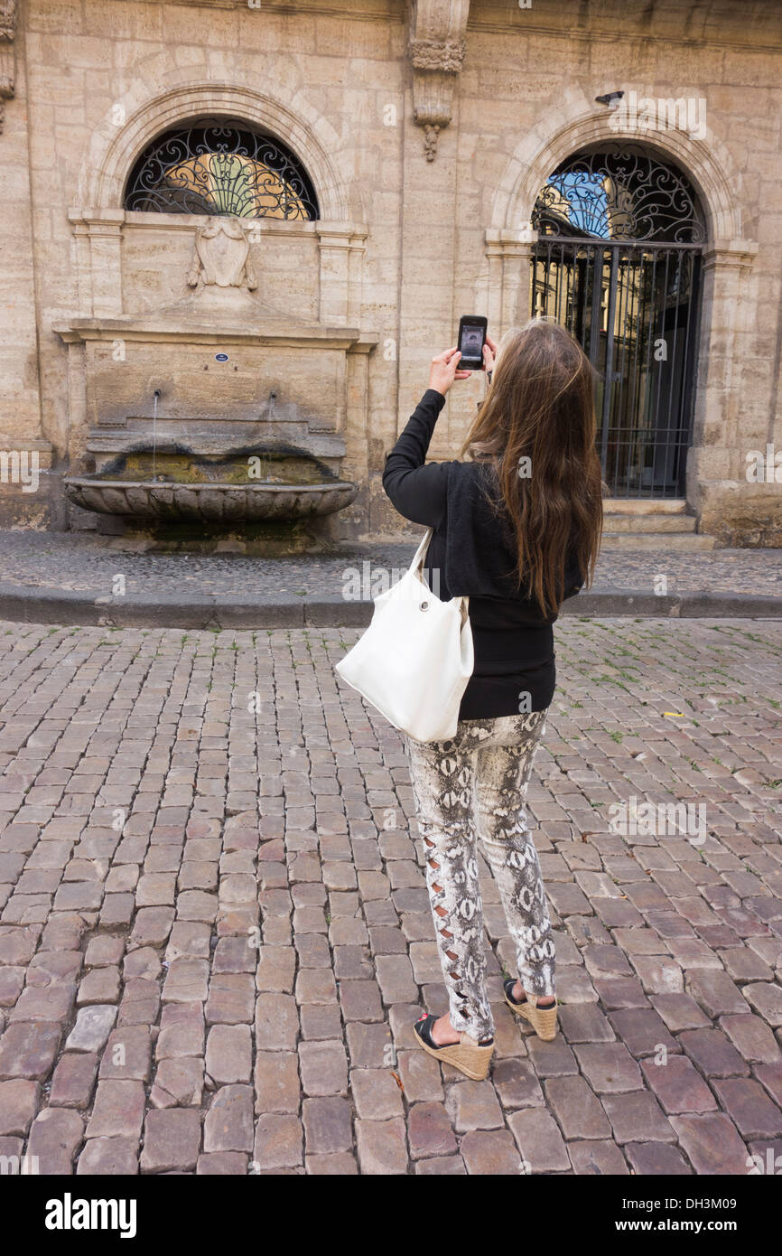 Tourist takes photo with her cell phone in picturesque town of Pezenas; Herault; Languedoc; France - Stock Image