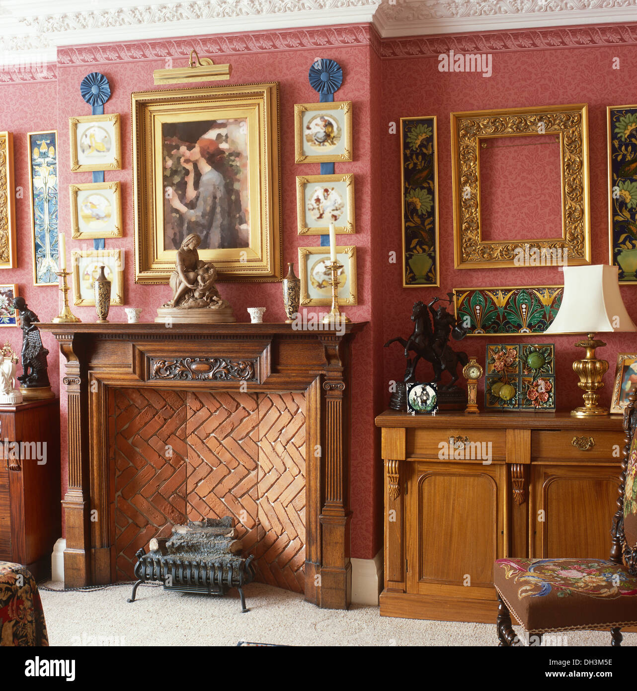 Pictures and carved wooden mantelpiece above fireplace with electric ...
