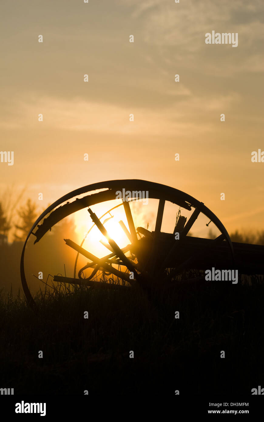 The sun rises behind a broken wagon wheel lying in a hay field. - Stock Image