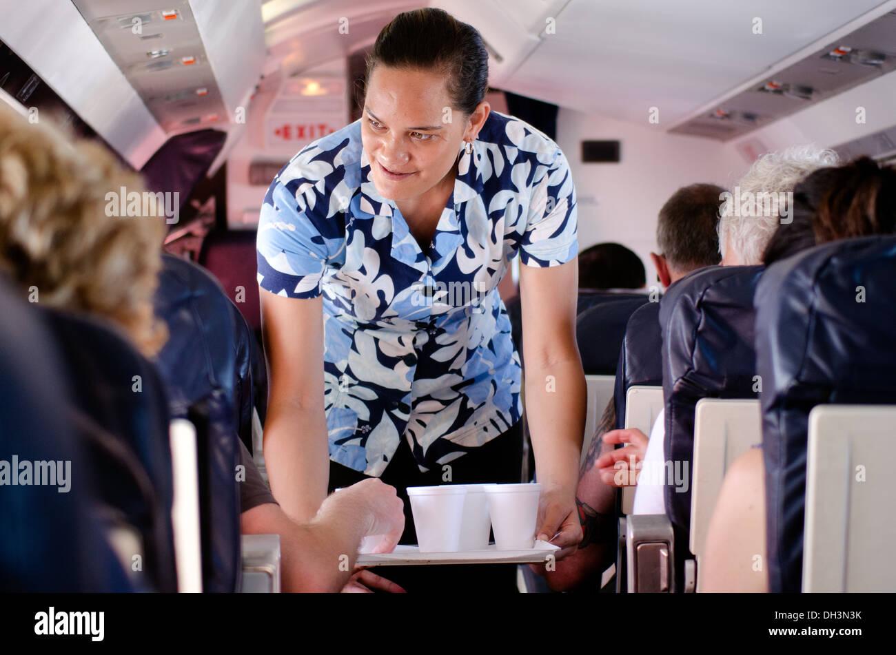 Air Rarotonga air hostess serves hot drinks during flight to Aitutaki lagoon Cook Islands - Stock Image