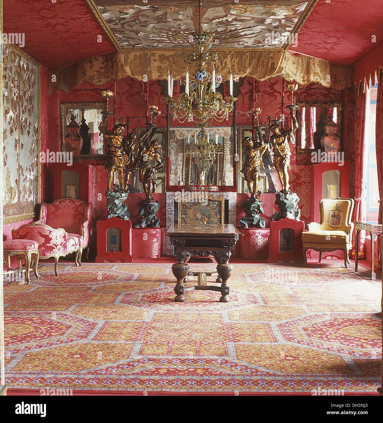 Opulent Red Dining Room With Ornate Ceiling And Gold Drapes And Mirror  Above Fireplace With Blackamoor Statues On Plinths