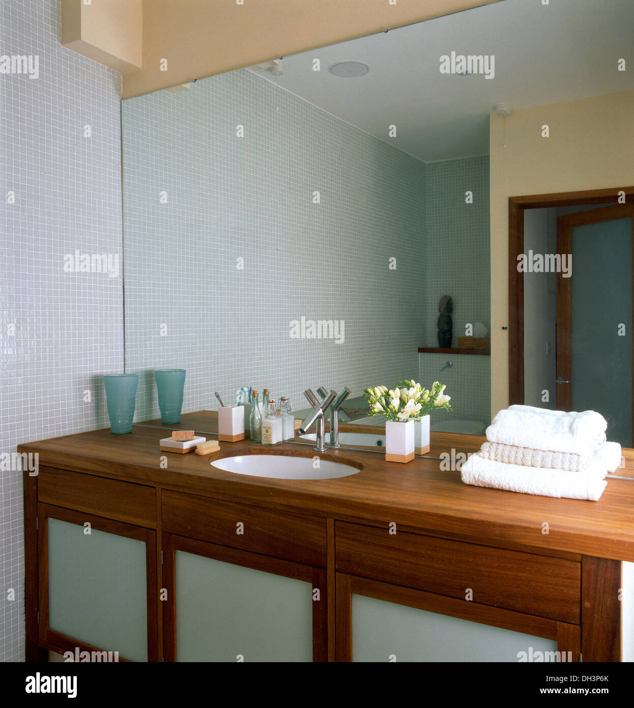 Mirrored wall above wooden vanity unit with under set basin in modern bathroom - Stock Image