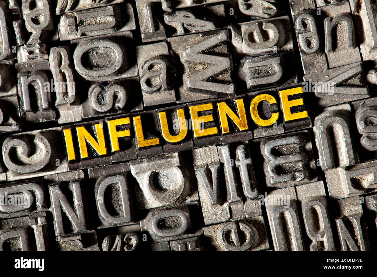 Old lead letters forming the word 'INFLUENCE' - Stock Image