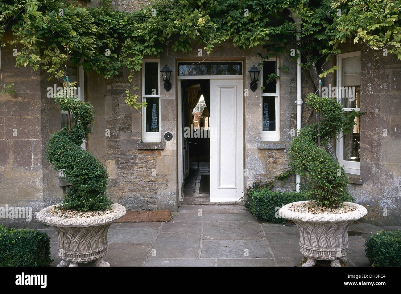 Spiral Topiary Box In Stone Urns In Front Of House With Open Front