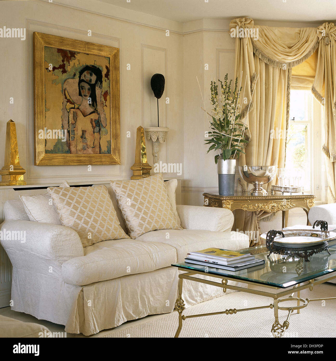 Large Gilt Framed Picture Above White Sofa With Silk Cushions In Opulent  Living Room With Silk Swagged+draped Curtains