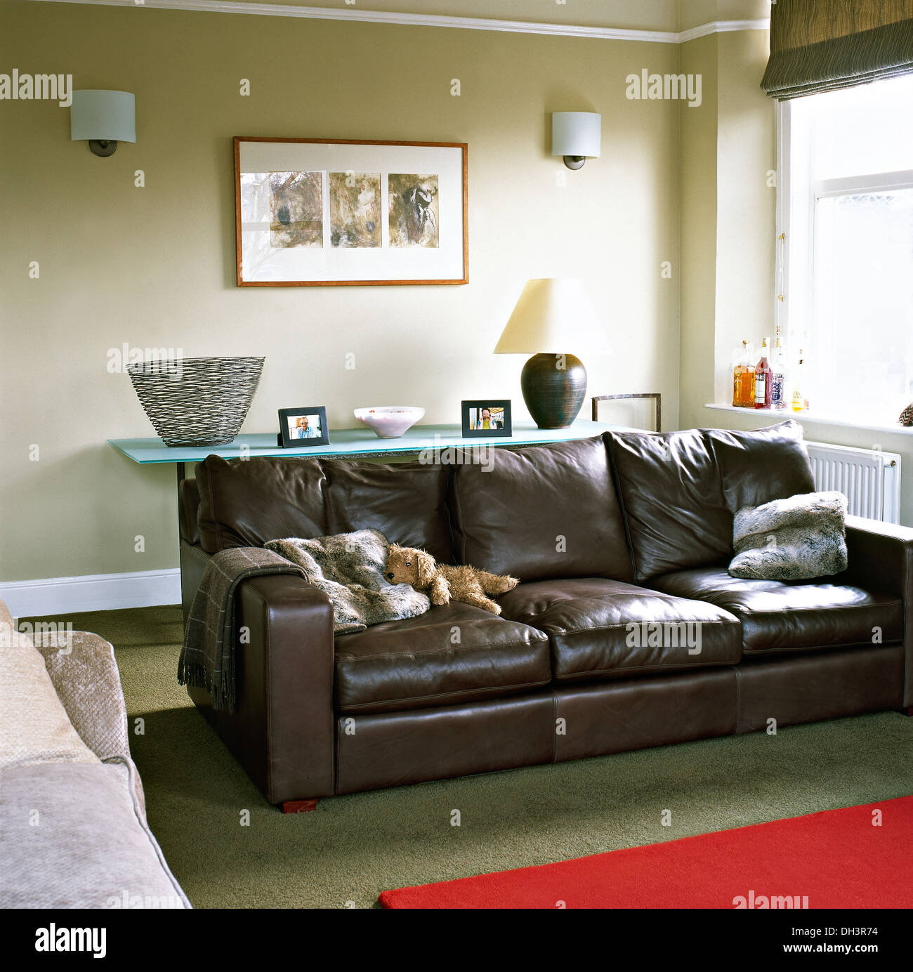 Brown leather sofa with faux fur cushions in modern living ...