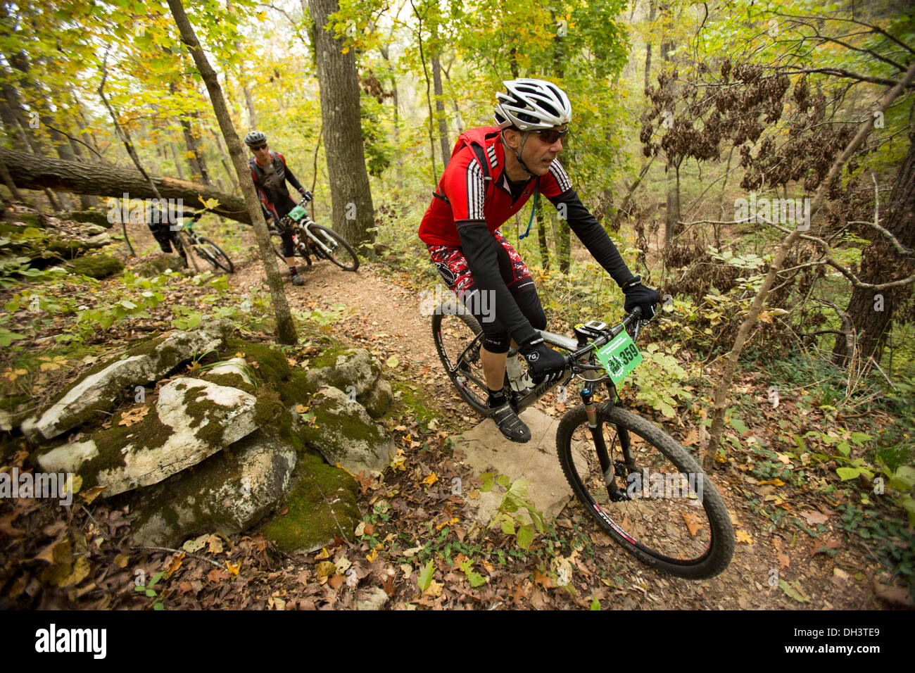 Mountain bikers ride along a forest trail system at Blowing Springs Park in Bella Vista, Arkansas. - Stock Image