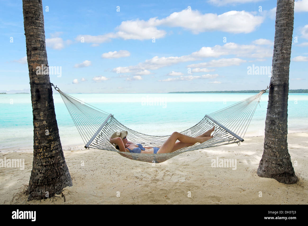 Happy woman relaxing on hammock on the beach during travel vacation on tropical island in Aitutaki lagoon, Cook Islands. - Stock Image
