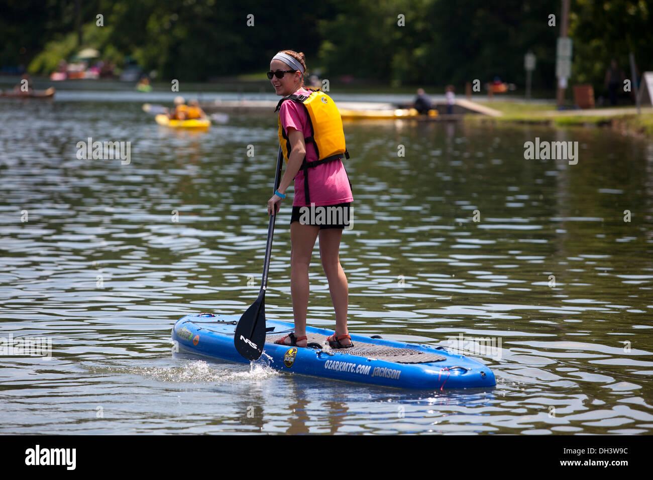 A single female paddle boarding on a lake in Bella Vista, Arkansas, USA. Stock Photo