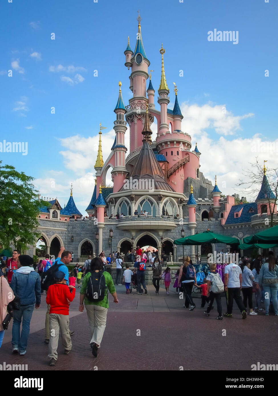Tourists walk towards Sleeping Beauty's castle at Disneyland Paris, France - Stock Image