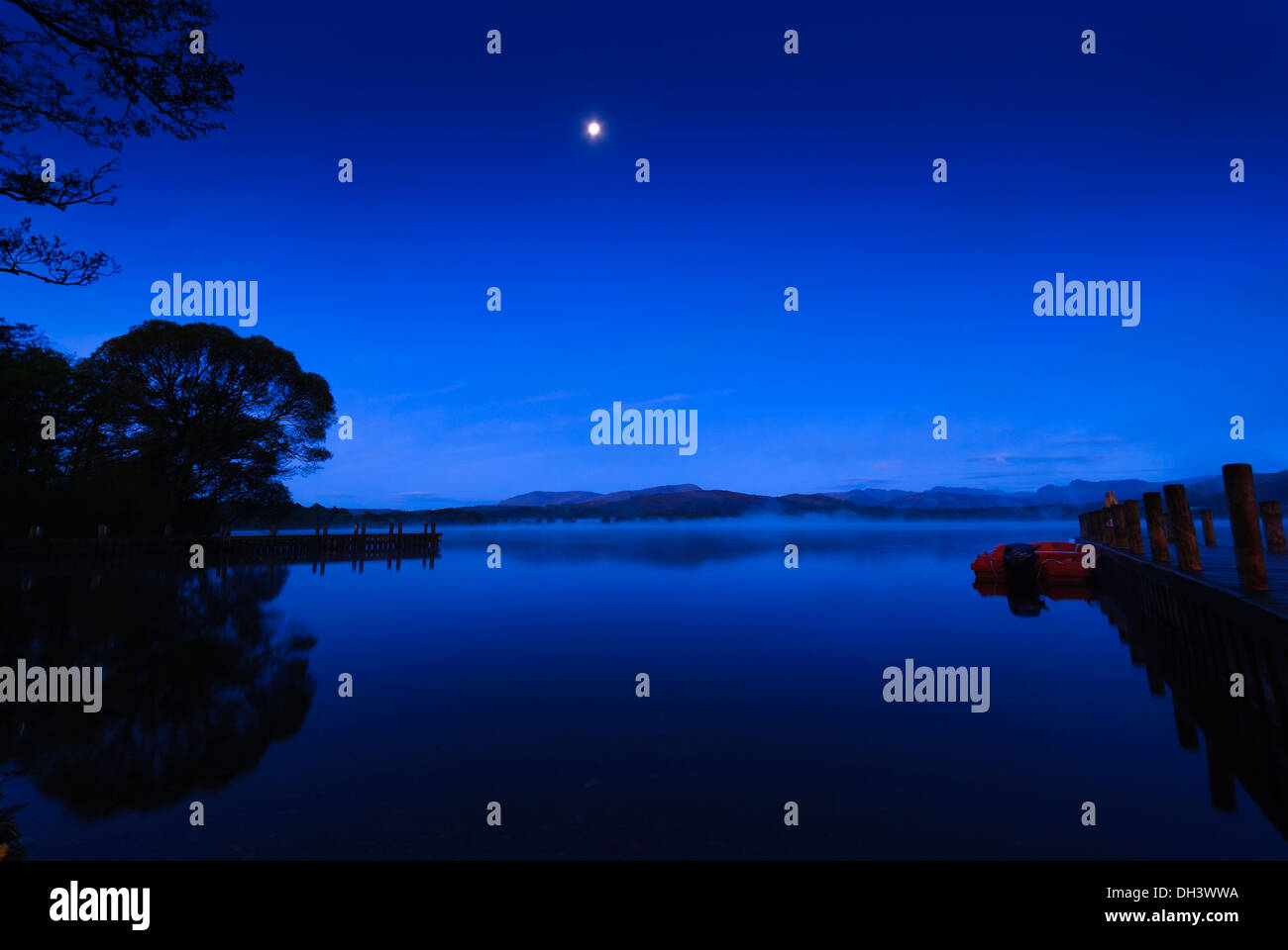 Very still waters on a moonlit shore of Lake Windermere In Cumbria before dawn with the moon in the picture and jetties. - Stock Image