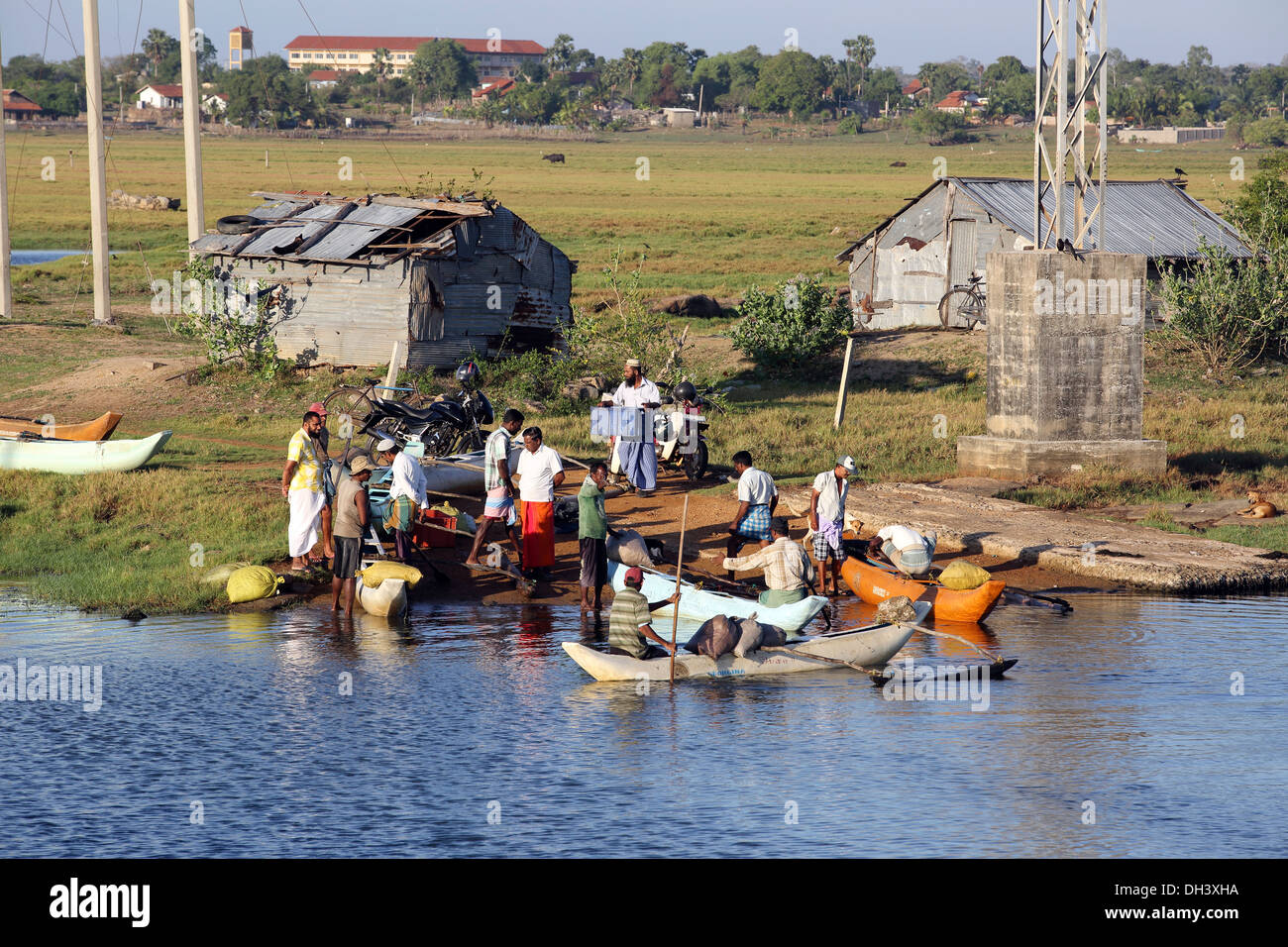 Sri Lankan fishermen returning with their catches in simple outrigger canoes to the shore of Arugam Lagoon. - Stock Image