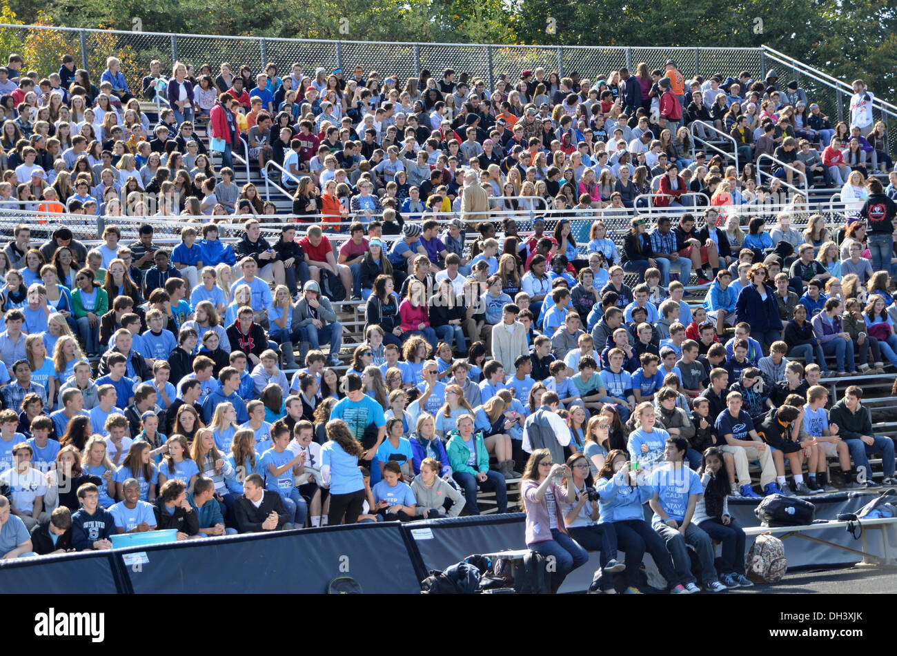 Crowd in the stands at a high school football game - Stock Image