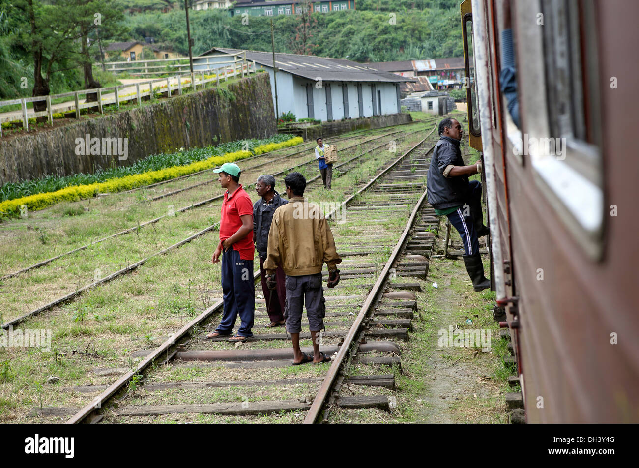 Men standing on train tracks at Nanu Oya train station in the Sri Lanka highlands - Stock Image