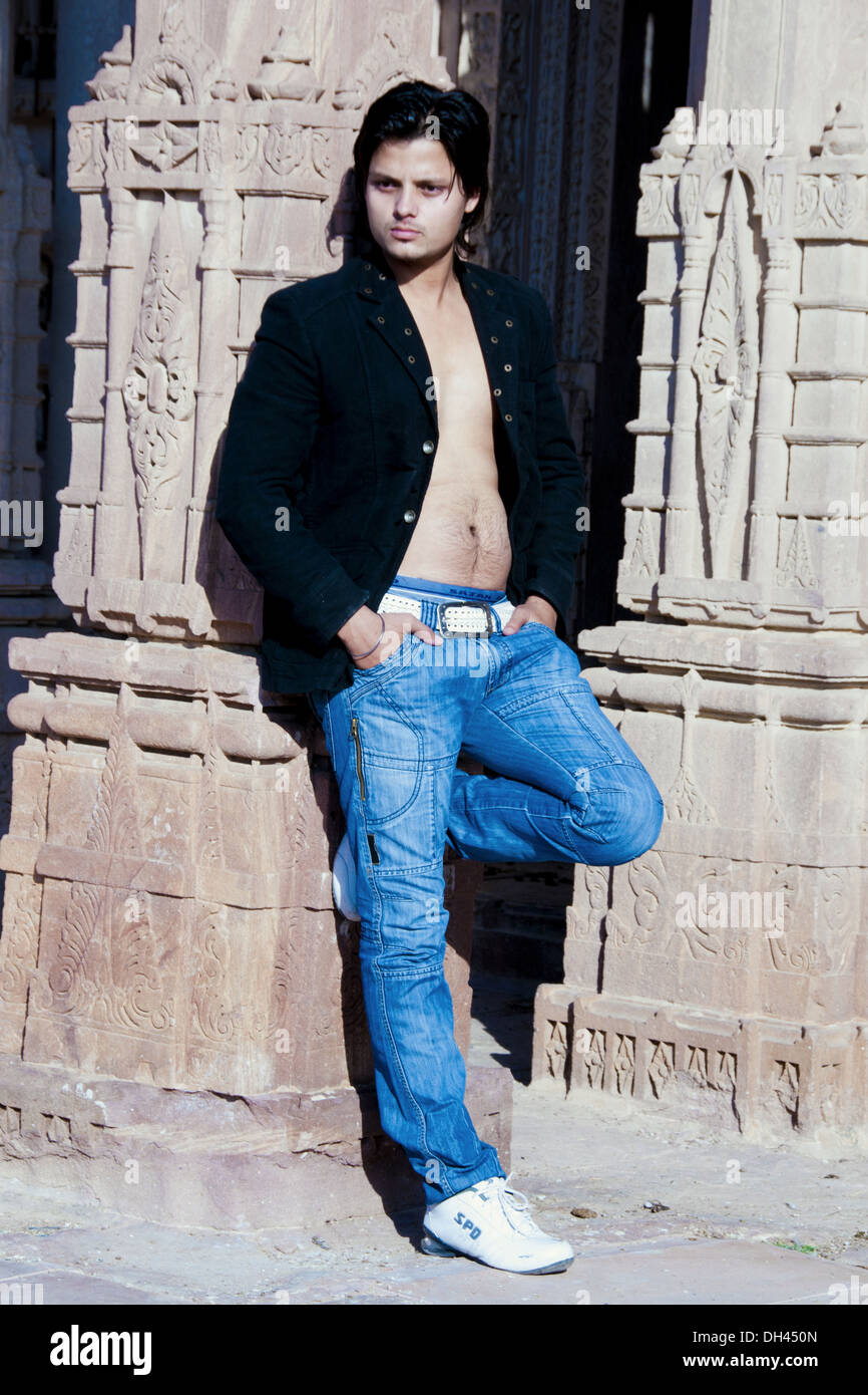 Man standing in blue jeans black jacket bare chest white shoes white belt   MR#786 - Stock Image