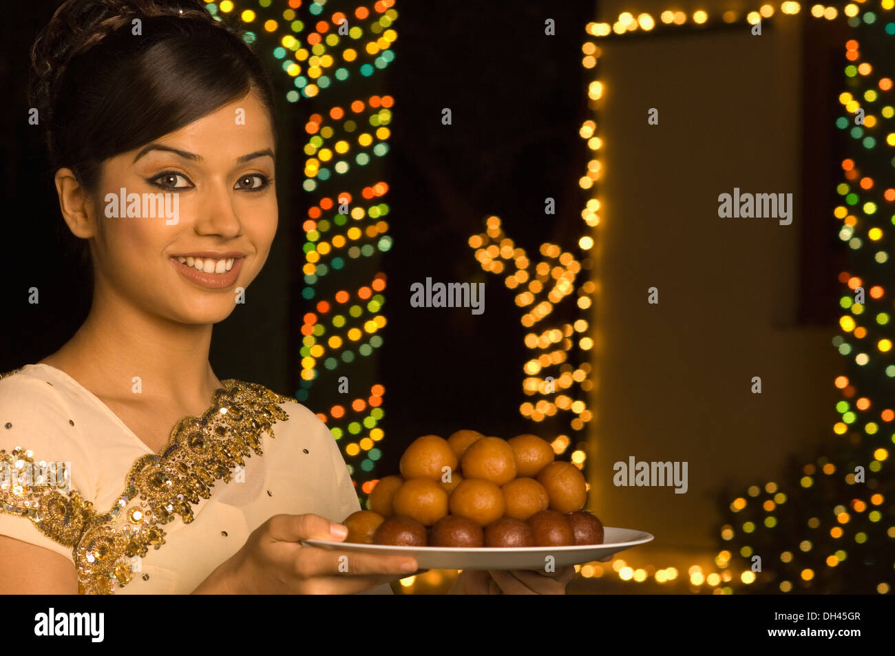 Woman holding sweets in a plate and smiling Stock Photo
