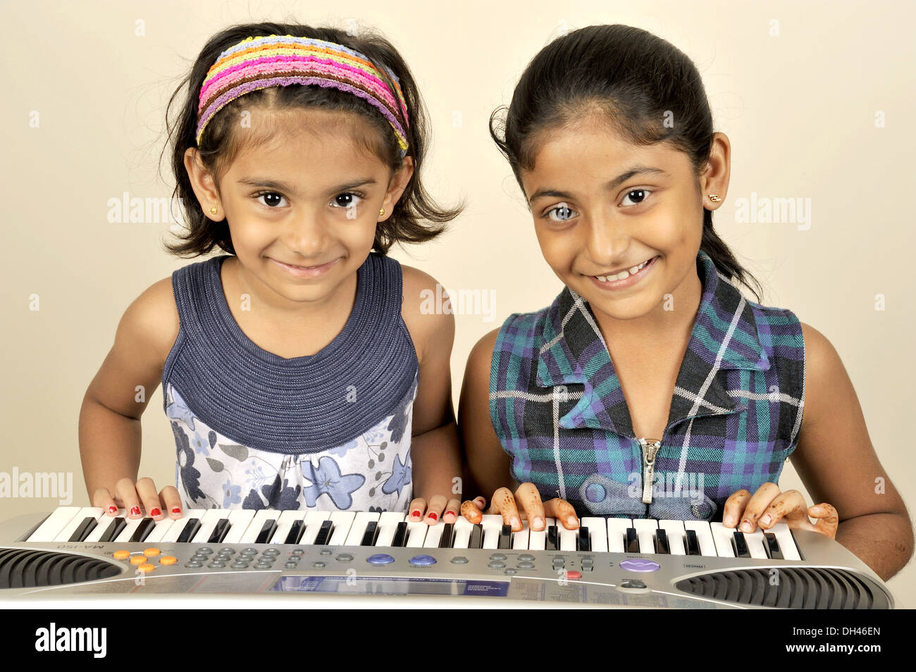 Two sisters friends girls playing piano MR#736L&682W - Stock Image
