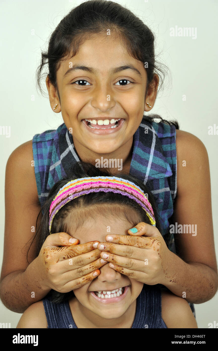 children girls sisters friends playing game hide and seek   MR#682W&736L - Stock Image