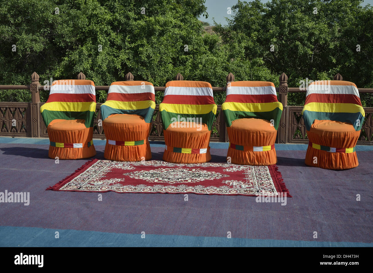 five empty vacant chairs and carpet outdoors on open terrace Jodhpur Rajasthan India Asia - Stock Image