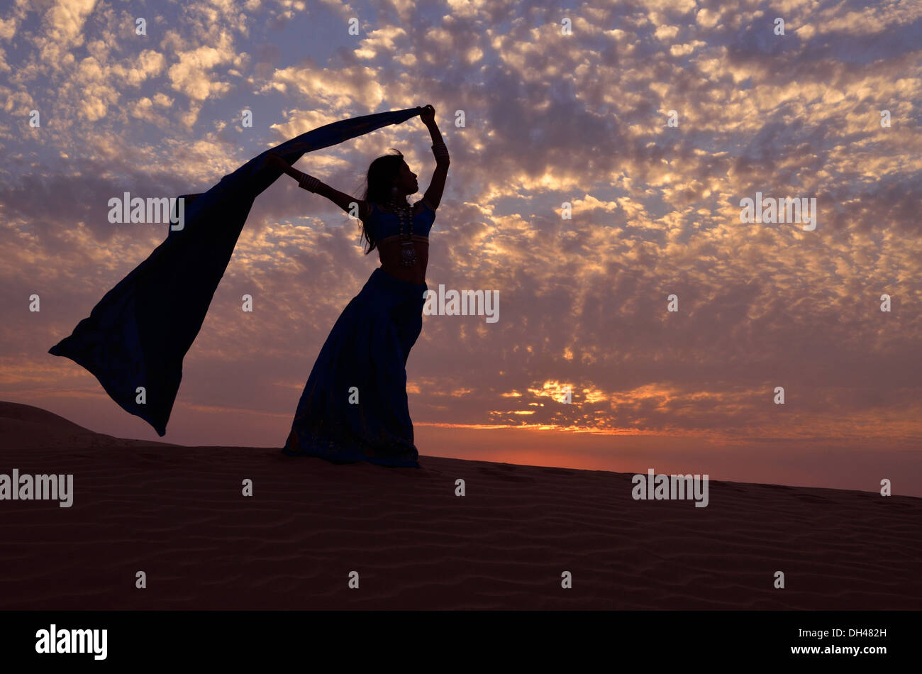 women saree sari dupatta scarf flying fluttering in the wind on desert sand dune Rajasthan India Asia - Stock Image