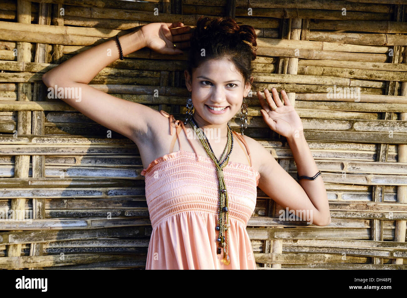girl giving pose in front of bamboo hut background at Rajahmundry Andesh Pradesh India MR#704K - Stock Image