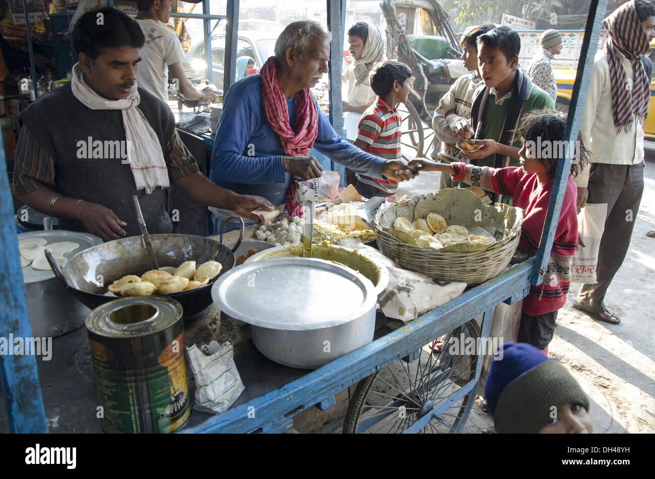vendor selling food fried bread vegetable chole bhature on pavement footpath at kolkata west bengal India - Stock Image