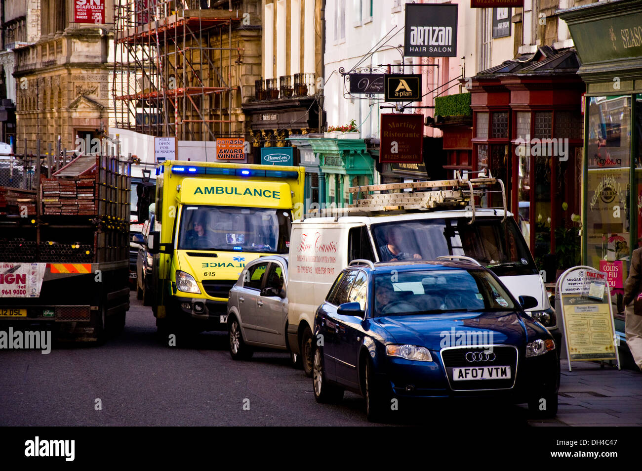 Ambulance on emergency call trying to squeeze through congested traffic on a busy street in Bath Somerset England - Stock Image