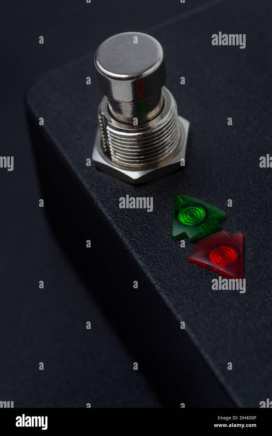 Black case with a push-button and two arrow-shaped indicator lights.   Boîtier noir avec bouton poussoir et voyants lumineux. - Stock Image