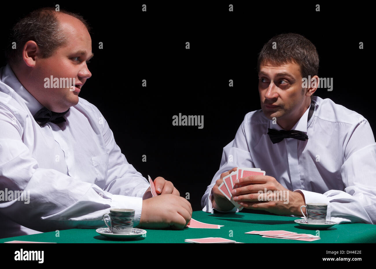 Two gentlemen in white shirts, playing cards - Stock Image